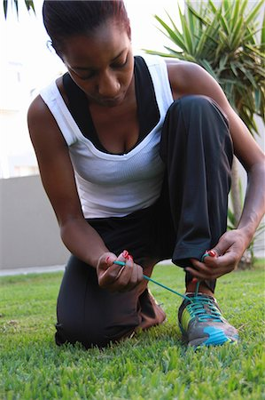 Young woman tying shoelaces, Johannesburg, South Africa Stock Photo - Premium Royalty-Free, Code: 682-07281299