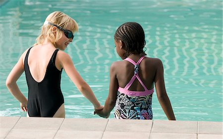 Two multi-racial girls going into a pool. Windhoek, Namibia. Stock Photo - Premium Royalty-Free, Code: 682-07281440