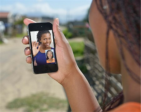 Mobile phone being used outdoors for a video call. Philippi, Cape Town, South Africa. Stock Photo - Premium Royalty-Free, Code: 682-07281552