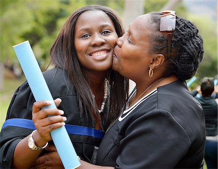 Proud mother kissing her daughter at her daughters graduation ceremony. Cape Town, South Africa. Stock Photo - Premium Royalty-Free, Code: 682-07281564