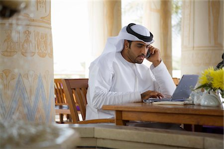 Arab Business Man using Mobile Phone and Computer, sitting on Patio Table in Restaurant Stock Photo - Premium Royalty-Free, Code: 682-02894124