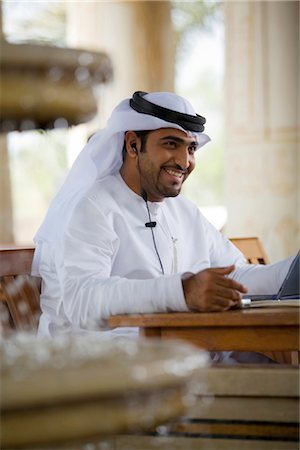 Smiling Arab Business Man Working on Laptop Computer Stock Photo - Premium Royalty-Free, Code: 682-02894125