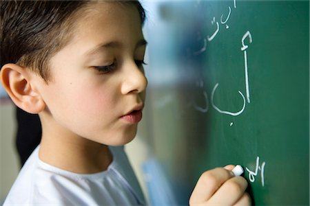 Boy Writing on Blackboard in Classroom Stock Photo - Premium Royalty-Free, Code: 682-02894157