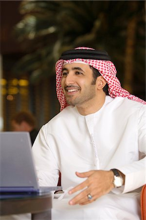 Arab Man Gesturing to Friend in Front of Laptop Computer Stock Photo - Premium Royalty-Free, Code: 682-02894169