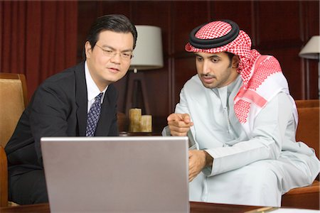 Arab Business Man and Asian Business Man Looking at Laptop Computer Screen Stock Photo - Premium Royalty-Free, Code: 682-02894282