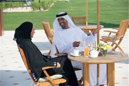 Smiling Arab husband and wife sitting on outdoor patio Stock Photo - Premium Royalty-Free, Code: 682-02894375