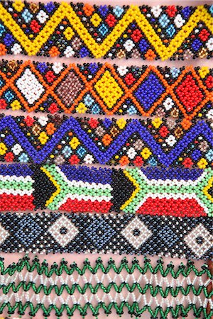 Dispaly of Brightly Coloured African Traditional Beaded Wristbands Including South African Flag Stock Photo - Premium Royalty-Free, Code: 682-02894985