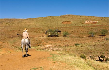 road landscape - Basotho man riding a pony along a track. Stock Photo - Premium Royalty-Free, Code: 682-02894996
