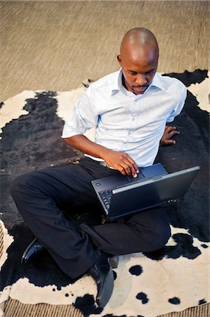 Businessman works on a laptop while sitting on an Nguni cow skin, for luck. Pretoria, South Africa Stock Photo - Premium Royalty-Free, Code: 682-02895194