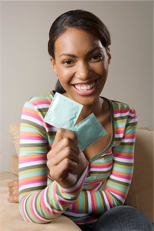 South African teen culture - Portrait of young woman holding condoms. Stock Photo - Premium Royalty-Free, Code: 682-02896198