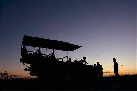 4x4 game viewer and tourists silhouetted at sunset, Okavango Delta, Botswana Stock Photo - Premium Royalty-Free, Code: 682-02891418