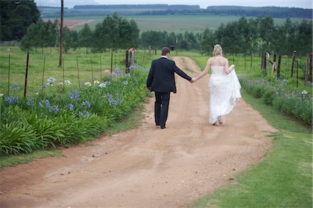 road landscape - Bride and Groom Walking on Dirt Road Stock Photo - Premium Royalty-Free, Code: 682-02892818