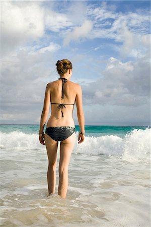 Young woman walking into ocean, dawn, Seychelles Stock Photo - Premium Royalty-Free, Code: 682-03285645