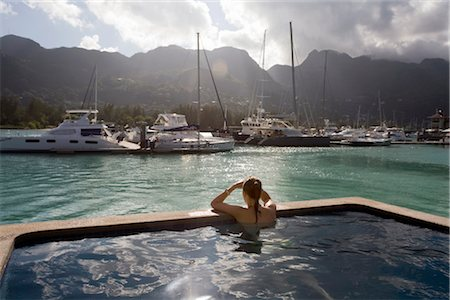 seychelles - Young woman in swimming pool  looking at yachts, Seychelles Stock Photo - Premium Royalty-Free, Code: 682-03285655