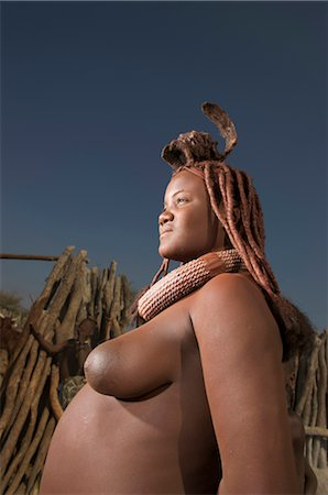 Low angle view of bare breasted Himba woman, Epupa Falls area, Kaokoland, Namibia Stock Photo - Premium Royalty-Free, Code: 682-03285684