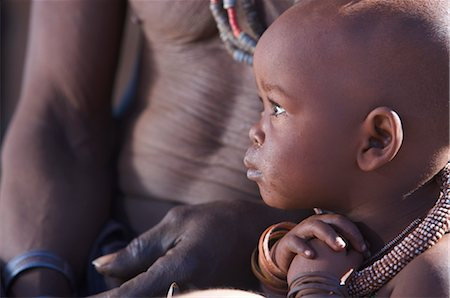 shy baby - Profile view of a Himba child and torso of man, Van Zyl's Pass area, Kaokoland, Namibia Stock Photo - Premium Royalty-Free, Code: 682-03285693