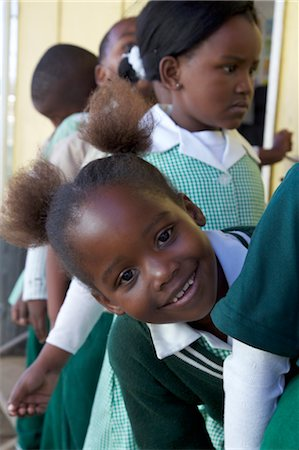 school girl uniforms - Close up shot of schoolgirl peeking out from the line, KwaZulu Natal Province, South Africa Stock Photo - Premium Royalty-Free, Code: 682-03643876