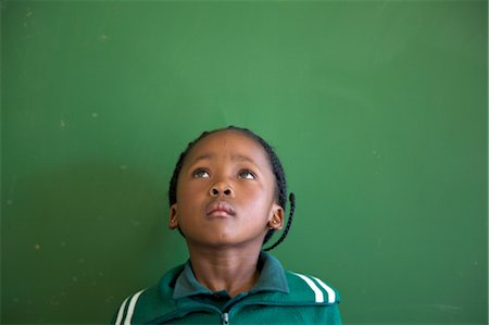 school girl uniforms - Schoolgirl stands in front of the classroom chalkboard, looking upward, KwaZulu Natal Province, South Africa Stock Photo - Premium Royalty-Free, Code: 682-03643871