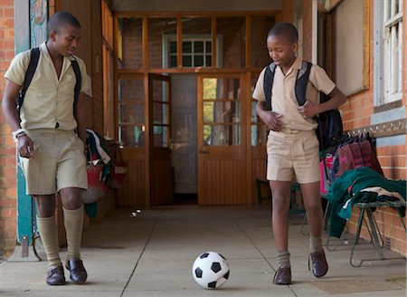 Two schoolboys kick a soccer ball outside their classroom, KwaZulu Natal Province, South Africa Stock Photo - Premium Royalty-Free, Code: 682-03643924
