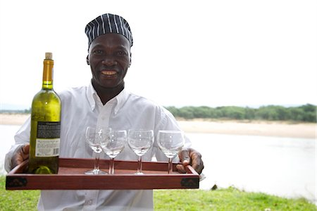 Portrait of a man serving wine at a safari camp, Luangwa Valley, Zambia Stock Photo - Premium Royalty-Free, Code: 682-03734850