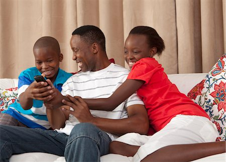 Man and children fighting over remote control, Johannesburg, South Africa Stock Photo - Premium Royalty-Free, Code: 682-03797991