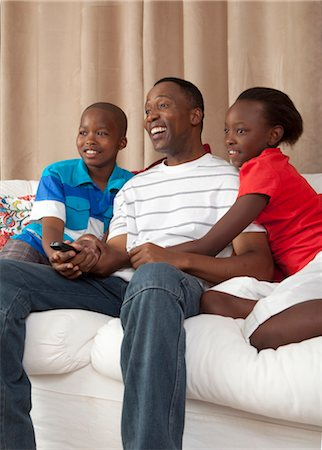 Man and children watching television together, Johannesburg, South Africa Stock Photo - Premium Royalty-Free, Code: 682-03797992