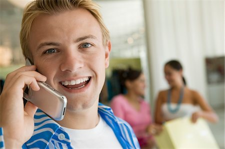 Young Man Using Cell Phone in clothing Store, portrait, close up Stock Photo - Premium Royalty-Free, Code: 694-03318485