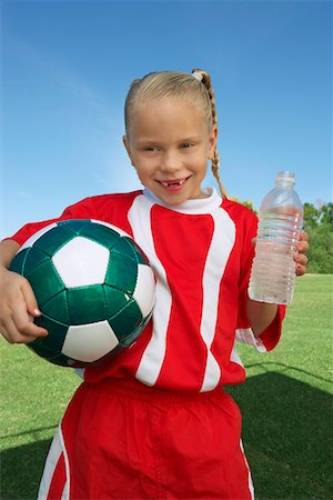 Girl (7-9 years) soccer player holding ball and water bottle, portrait Stock Photo - Premium Royalty-Free, Code: 694-03327044