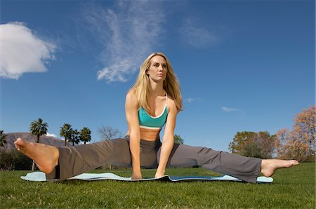 Young woman performing yoga exercises in park Stock Photo - Premium Royalty-Free, Code: 694-03327463