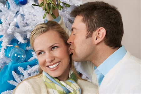 Man kissing woman under mistletoe Stock Photo - Premium Royalty-Free, Code: 694-03327521