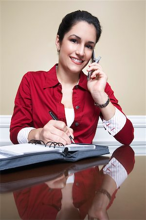 planner - Business woman using mobile phone and writing in diary in office, portrait Stock Photo - Premium Royalty-Free, Code: 694-03327620
