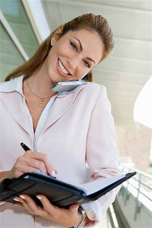 planner - Businesswoman writing in planner while using cell phone outdoors, portrait Stock Photo - Premium Royalty-Free, Code: 694-03327969