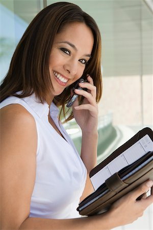 planner - Woman using cell phone holding planner, portrait Stock Photo - Premium Royalty-Free, Code: 694-03327977