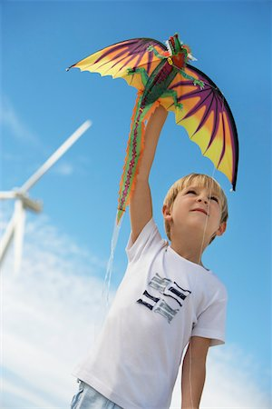 Boy (7-9) playing with kite at wind farm Stock Photo - Premium Royalty-Free, Code: 694-03328219