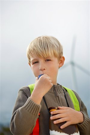 Boy (7-9) blowing toy whistle at wind farm, portrait Stock Photo - Premium Royalty-Free, Code: 694-03328231