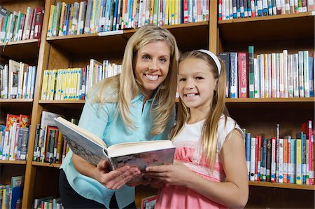 School girl and teacher holding book in library, portrait Stock Photo - Premium Royalty-Free, Code: 694-03330078