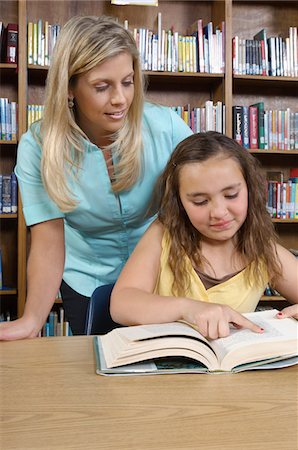School girl reading book with teacher in library Stock Photo - Premium Royalty-Free, Code: 694-03330093