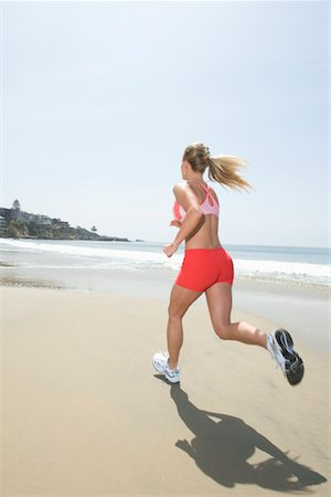 Woman jogging along beach Stock Photo - Premium Royalty-Free, Code: 694-03332369