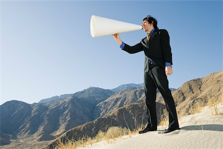 Businessman Using Megaphone in Desert Stock Photo - Premium Royalty-Free, Code: 694-03332423