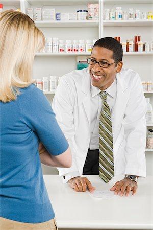 Woman picking up prescription drugs at pharmacy Stock Photo - Premium Royalty-Free, Code: 694-03332782