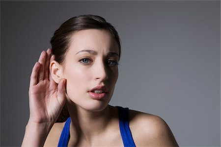 Brunette with hand behind ear Stock Photo - Premium Royalty-Free, Code: 694-03333054
