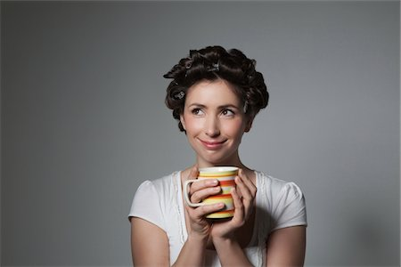 quirky - Coy young woman with hair curlers holding cup Stock Photo - Premium Royalty-Free, Code: 694-03333060