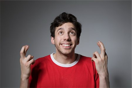 quirky - Young man in red top looking up with fingers crossed Stock Photo - Premium Royalty-Free, Code: 694-03333063