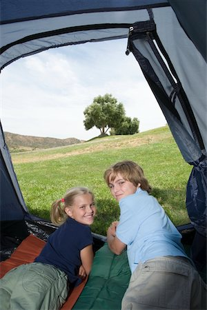 Brother and sister lie in a tent, looking back over their shoulders Stock Photo - Premium Royalty-Free, Code: 694-03440990