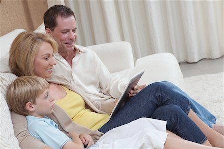 Family of three sit reading a digital book Stock Photo - Premium Royalty-Free, Code: 694-03557958