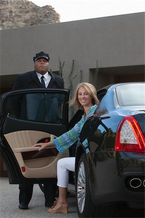 Chauffeur helps woman from luxury vehicle Stock Photo - Premium Royalty-Free, Code: 694-03557979