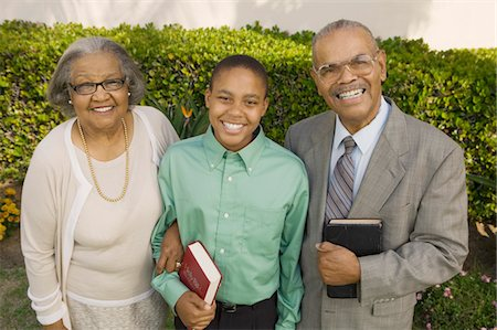 Christian Grandparents and Grandson in garden holding Bibles, portrait Stock Photo - Premium Royalty-Free, Code: 694-03692507