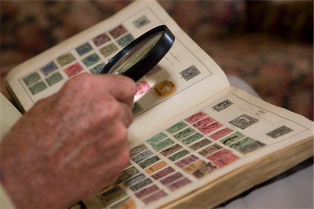 stamp - Senior man looks at stamp collection with magnifying glass Stock Photo - Premium Royalty-Free, Code: 694-03783265