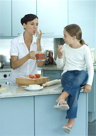 preteen thong - Girl sitting on kitchen counter while mother holds up container of tomato sauce Stock Photo - Premium Royalty-Free, Code: 695-05764214
