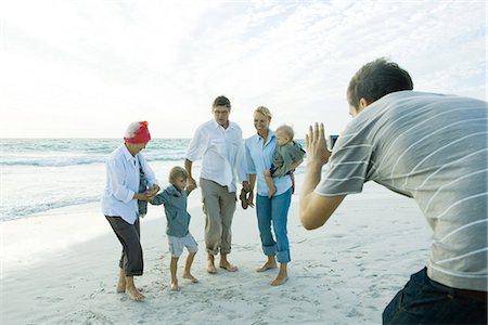 Family on beach, man taking photo Stock Photo - Premium Royalty-Free, Code: 695-05766084